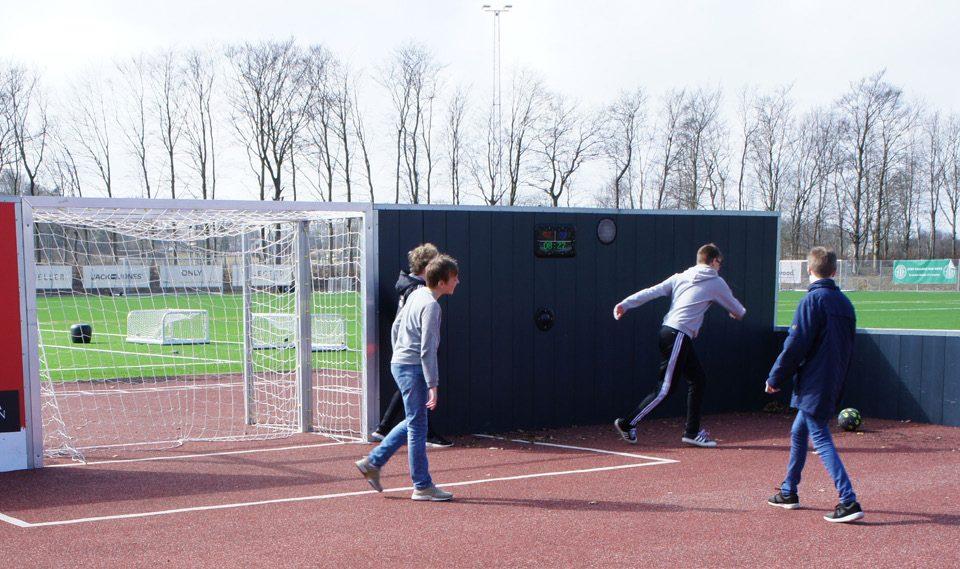 Voetballende jongens bij een scoreboard